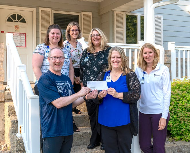 Lisa Dahl Executive Director Prairie Lakes Healthcare Foundation, front, center, receive a $3,000 check from Prairie Lakes Healthcare System employees, back row, Jennifer Bender, middle row, Bonnie Cordell, Sarah Bruning, front, Dan Reiffenberger and Jessi Eidson. The donation is from funds raised at the 24th Annual Hospital Hill Run on June 12. The donation is for the Caring Club House, which is for out-of-town parents, families and caregivers receiving services through Prairie Lakes.
