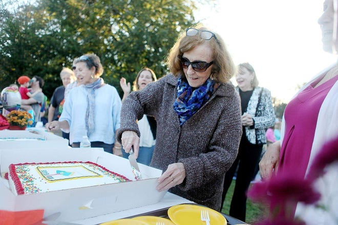 Alyce Deveau cuts a cake during the town's celebration of the Swampscott Public Library's 100th birthday in 2017.