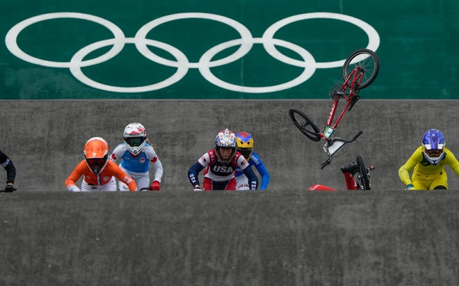 Felicia Stancil of the United States, center, looks ahead as the bike of teammate Alise Willoughby of the United States flies in the air after she crashed, in the BMX Racing semifinals at the 2020 Summer Olympics, Friday, July 30, 2021, in Tokyo, Japan. (AP Photo/Ben Curtis)
