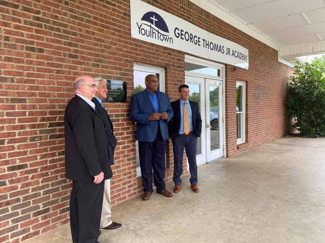 Youth Town CEO Joe Fote, Ambassador Nick Pappas, West Tennessee Healthcare CEO James Ross and Youth Town COO Nick Summar pose for photos in front of the George Thomas Jr. Academy on Youth Town's campus on Friday, July 30, 2021.