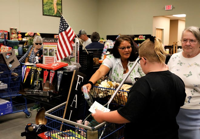 Carla Bush, center, shops with her grandchild during the grand opening of the Goodwill at the Lake Friday, July 30. Along with the usual donated items, the newly renovated Goodwill store in Buckeye Lake offers a variety of outdoor sporting goods and equipment.