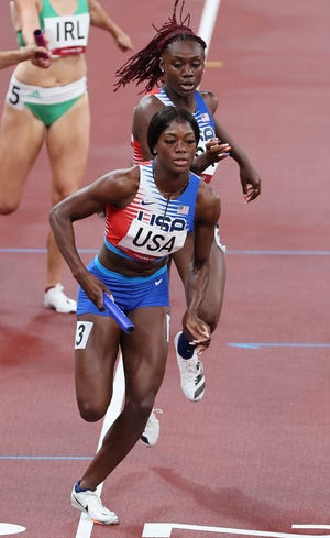 USA's Lynna Irby (rear) and Taylor Manson compete in the mixed 4x400m relay heats during the Tokyo 2020 Olympic Games at the Olympic Stadium in Tokyo on July 30, 2021.