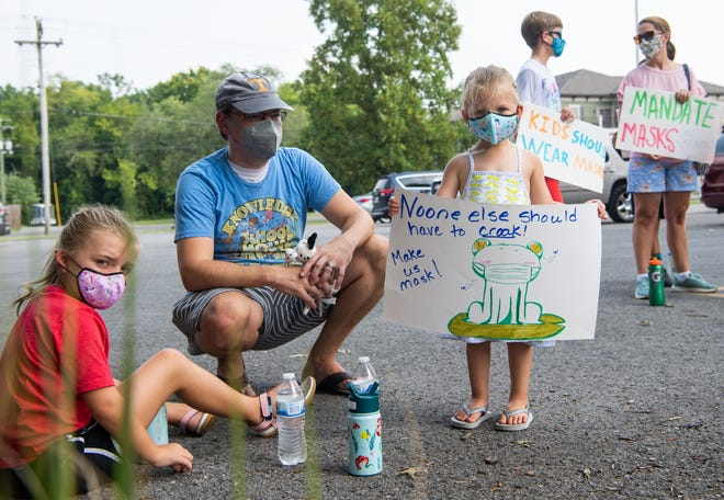 Benton McDonough and his daughters, Lily, 3,  and Lucy, 6, hold signs supporting masks in schools at the Williamson County Administrative Complex in Franklin, Tenn., Thursday, July 29, 2021.