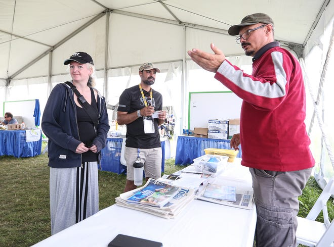 Marie Cassavant of Milwaukee and Hamed Sadabadi of Tehran, Iran, listen to International Visitor Tent volunteer Steve Kiss of Hungary on Friday, July 30, 2021, during the EAA AirVenture 2021 fly-in convention at Wittman Regional Airport in Oshkosh.
