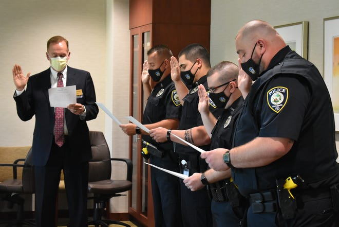 Craig Kinyon (from left), president and CEO of Reid Health, administers oaths to new police officers Dereck Tipton, Braydon Bolos, Troy McCauley and Cody Hahn.