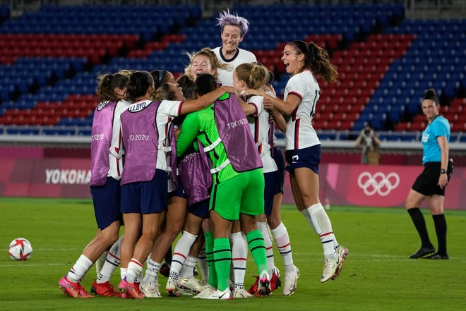 United States' players celebrate after defeating the Netherlands in a penalty shootout during a women's quarterfinal soccer match at the 2020 Summer Olympics, Friday, July 30, 2021, in Yokohama, Japan. Megan Rapinoe, top center, a Palo Cedro native who attended Foothill High School, jumps for joy during the celebration.