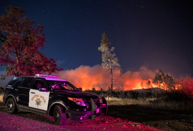 In this Sept. 28, 2020, file photo, a California Highway Patrol officer watches flames visible from the Zogg Fire near Igo, Calif. Pacific Gas & Electric will face criminal charges because its equipment sparked the wildfire that killed four people and destroyed hundreds of homes, Shasta County District Attorney Stephanie Bridgett announced Thursday, July 29, 2021.