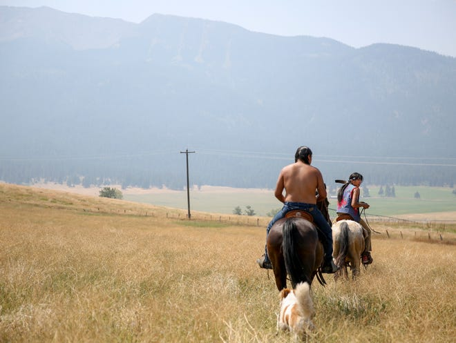 """Leland Whiteplume and Farley Eagle Speaker ride horses on Am'sáaxpa or """"the place of boulders,"""" on Thursday."""