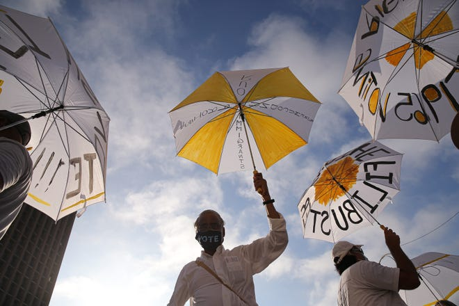 Attendees hold up white and yellow umbrellas with slogans on them before the start Saturday of the last leg of a 27-mile march from Georgetown to the Capitol to protest proposed new voting legislation.