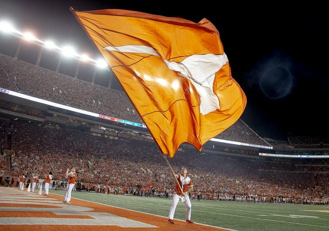 A cheerleader waves a giant Longhorns flag in the end zone at Royal-Memorial Stadium during the 2019 game against Kansas. Texas will welcome some new opponents as part of the upheaval in college athletics.