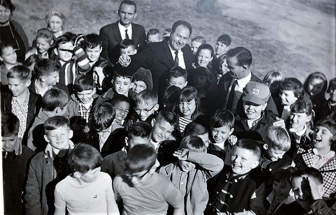 Columbia County school superintendent John Pierce Blanchard (center) looks up from a crowd of young students.