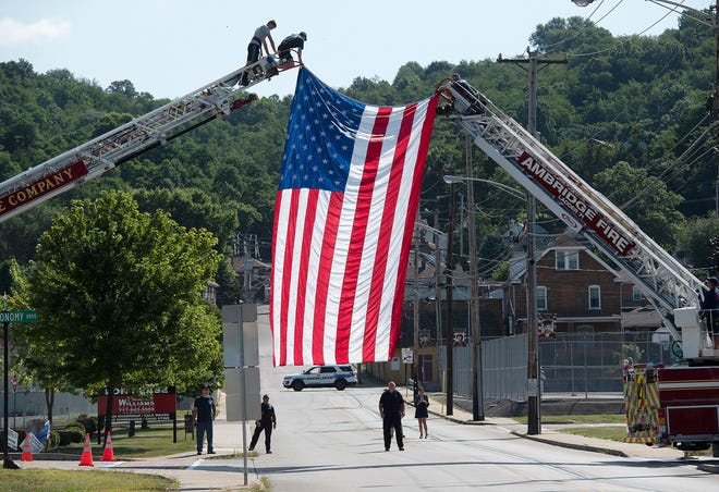 """Members of the Ambridge Fire Department hang a flag across 1th Street to welcome a """"Ride to Remember,"""" a traveling police memorial, Saturday morning in Ambridge."""
