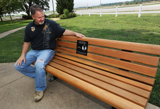 Jake Feil talks about the bench that is dedicated to his uncle Henry Lee Fisher, which is installed at the Veterans Memorial Walkway in Pioneer Park in Haven.
