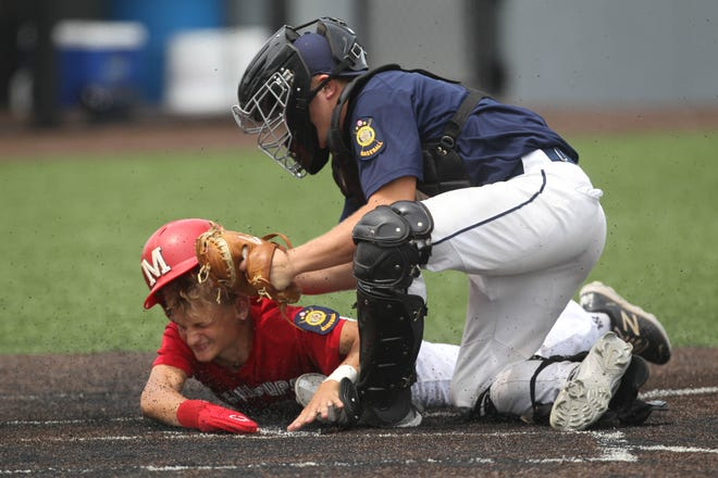 Salina Hawks catcher Brooks Richardson, right, tags out McPherson runner Brock Burgess at home plate during the championship game of the Kansas Junior American Legion state tournament Saturday at Dean Evans Stadium.