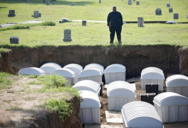 Graves Public Oversight Committee Chair J. Kavin Ross views remains in a mass grave as they are reinterred at Oaklawn Cemetery on Friday in Tulsa. The mass grave was discovered while searching for victims of the Tulsa Race Massacre.