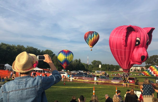 Anya Bobrinskaya of Williamsburg, Virginia, who is visiting in-laws in the area, photographs the lifting off of several hot air balloons Friday at the Pro Football Hall of Fame Enshrinement Festival Balloon Classic. The event continues through Sunday.