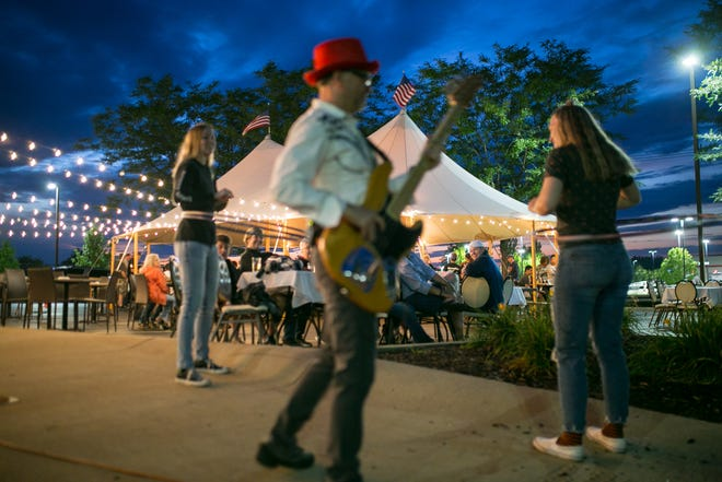 Siblings Emilie and Jak Reemtsma of Mesa, Arizona, who are visiting local relatives, hoola hoop while others enjoy a meal and live music by Prime Time Live Band under a big tent outside at GreenFire Restaurant Bar & Bakery Friday, July 30, 2021, in Rockford.