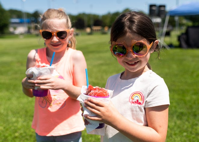 From left, Addison Ford, 9, and McKinley Ford, 6, enjoy snow cones during the Worcester Food Truck Throwdown on Saturday at Beaver Brook Park.