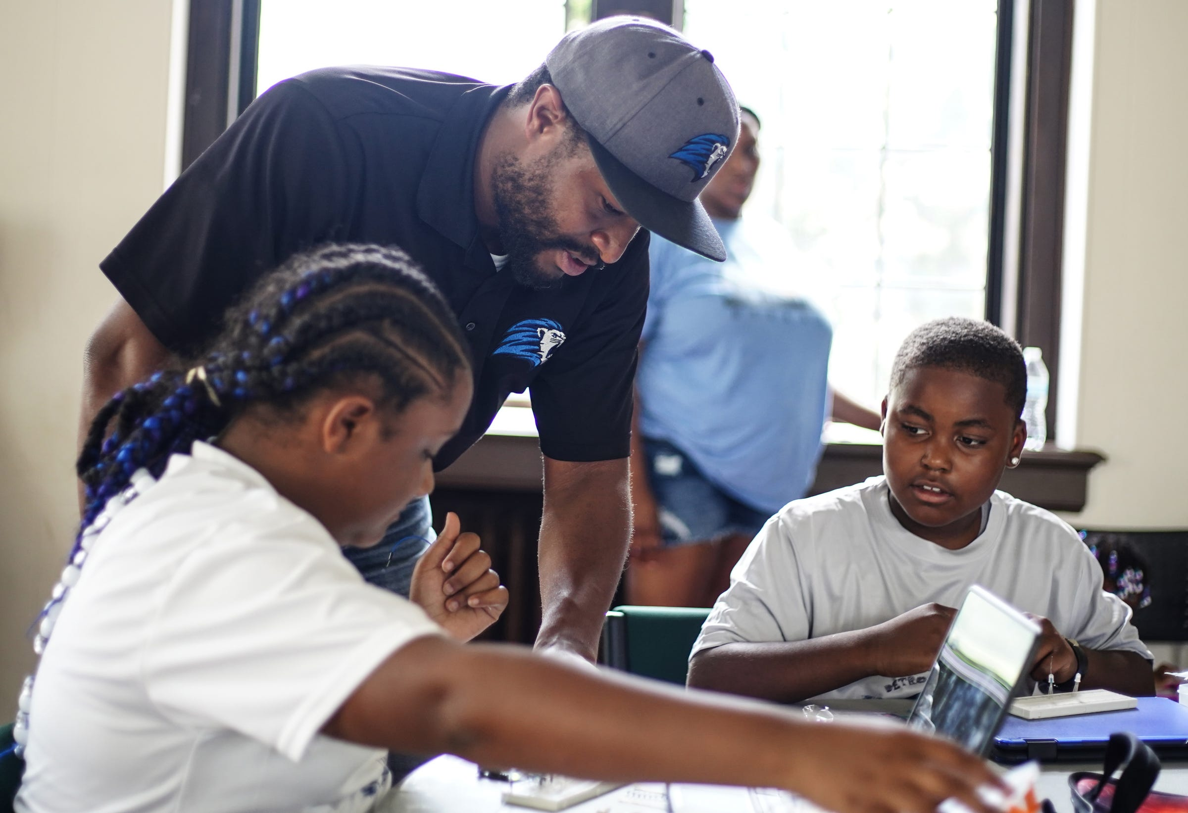 Devon Buskin, founder of Detroit City Lions watches Gabrielle Thomas, 10, of Detroit (left) and Dion Reaves, 8, of Detroit work on their robotics project at Marygrove College in Detroit on July 29, 2021. Detroit City Lions, a youth program founded by Devon Buskin is more than a youth football program. The program offers robotics classes, volleyball, musical arts along with football and cheer.