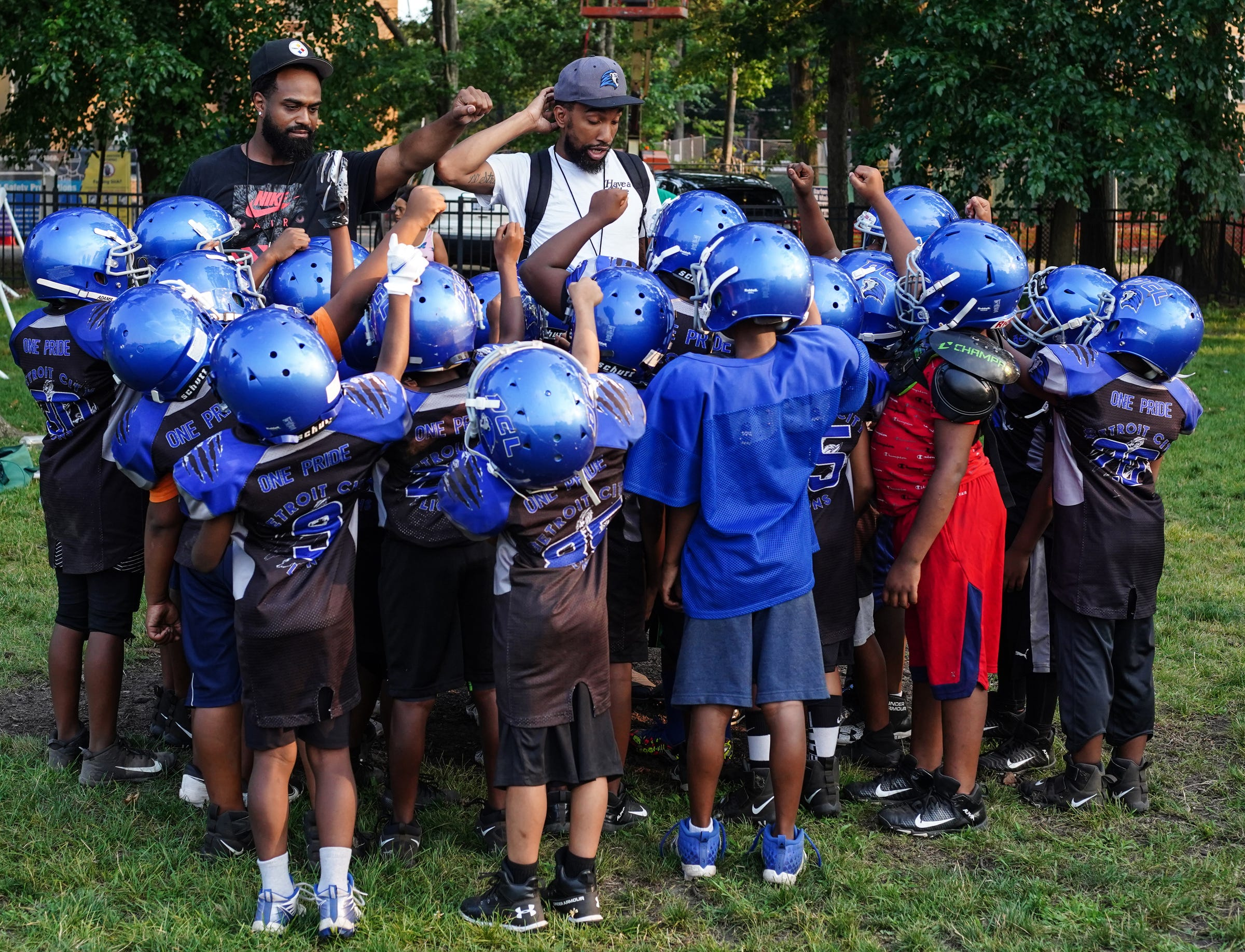 Detroit City Lions football team huddle at practice at Marygrove College in Detroit on July 29, 2021. Detroit City Lions, a youth program founded by Devon Buskin is more than a youth football program. The program offers robotics classes, volleyball, musical arts along with football and cheer.