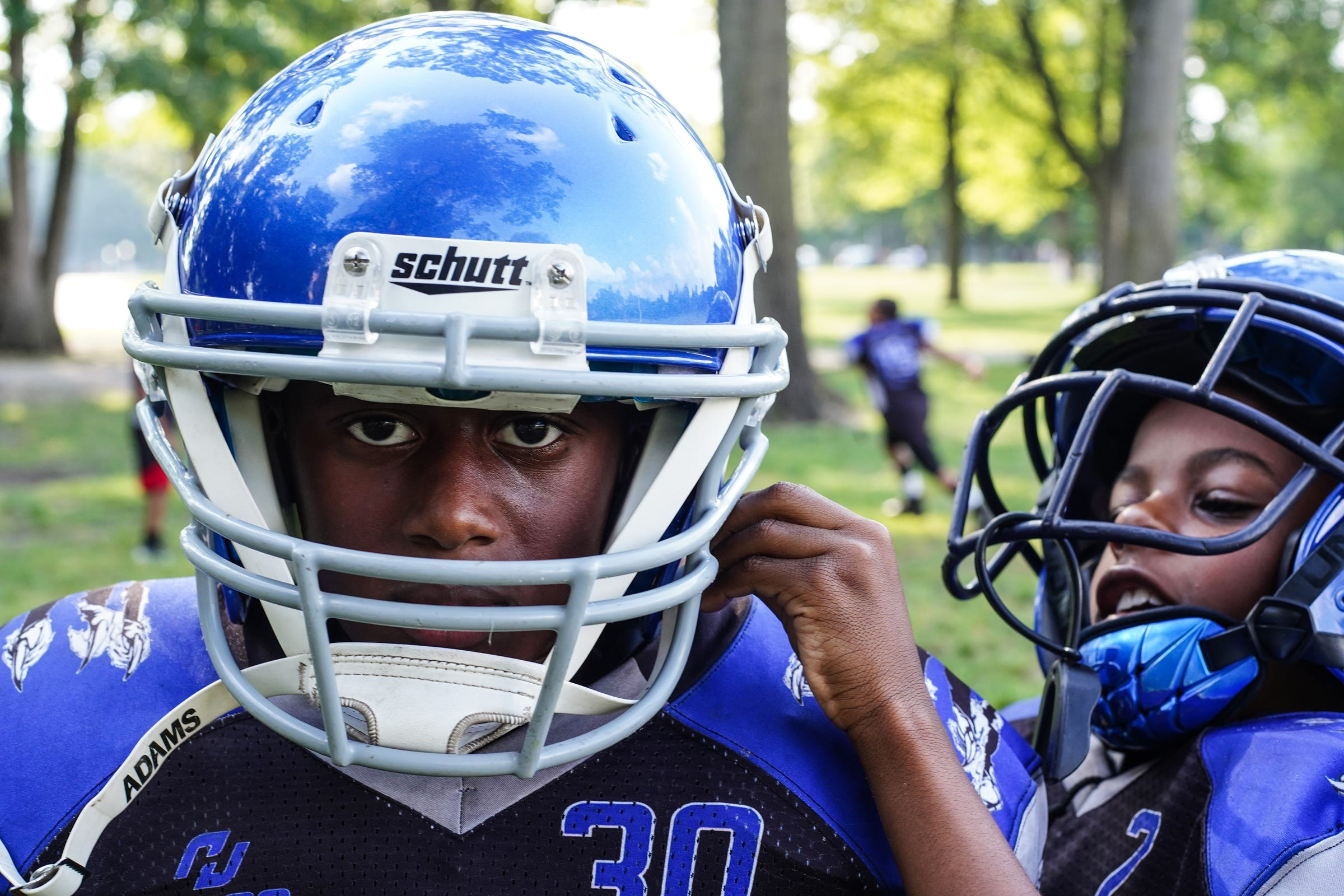 Javon Phillips, 8, of Detroit (right) straps Akeem Crowder, 8, of Detroit helmet before practice at Marygrove College in Detroit on July 29, 2021. Detroit City Lions, a youth program founded by Devon Buskin is more than a youth football program. The program offers robotics classes, volleyball, musical arts along with football and cheer.