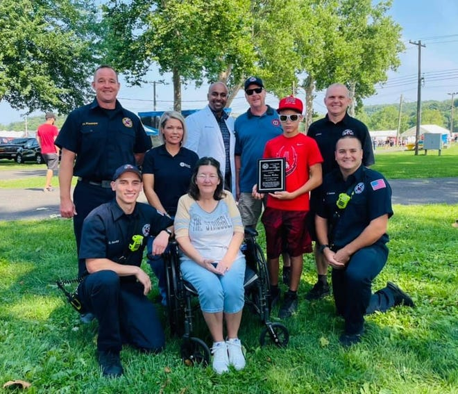 Traven Miller, in red, was recognized July 24 for calling 911 to save his grandmother, Debra Gilbert (seated) last November after she experienced cardiac arrest. Lancaster firefighter paramedics and representatives from Fairfield Medical Center presented Traven with the Lifesaver Award during the Lancaster Festival Fair Day.