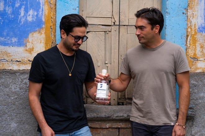 Matthew Hechter, a la izquierda, y Christopher Brandon, a la derecha, comparten una botella de tequila tepuzán en San Julián, México.