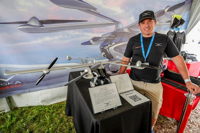 Guy Kaplinsky of Los Angeles poses during EAA AirVenture in Oshkosh with a model of an electric flying car that he developed.