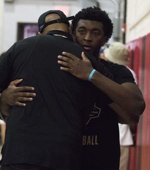 Hillcrest Prep senior Kyree Walker gets a little love from a friend as he watches a game during the Section 7 Basketball tournament at Brophy Prep High School in Phoenix, Friday, June 21, 2019.