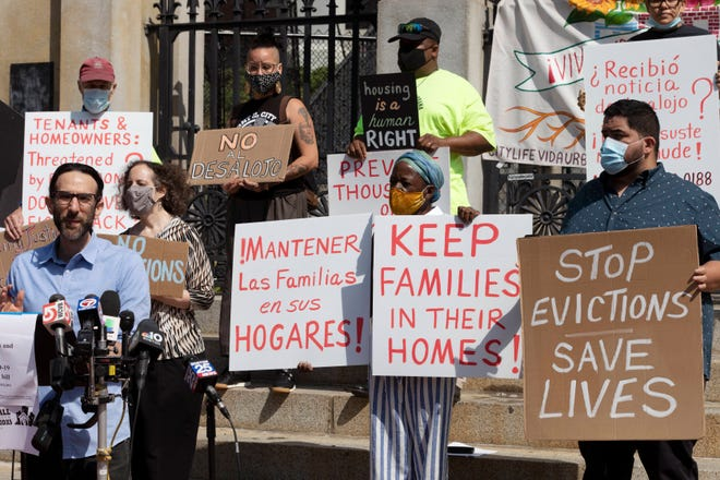 Protesters hold signs opposing evictions on July 30, 2021, in Boston.