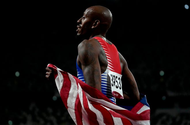 Vernon Norwood carries the American flag after he anchored the U.S. team to a bronze medal in the inaugural mixed 1,600-meter relay Saturday at the Olympics in Tokyo. Norwood ran collegiately for South Plains College and LSU.