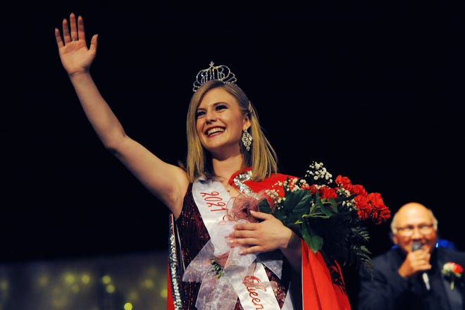 2021 Greater Alliance Carnation Festival Queen Torrie Forrest takes her first walk after being crowned queen as emcee Jimmy Korleski sings Saturday, July 31, 2021, on the stage at Alliance High School.