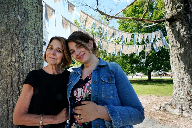 Widow Marcy Jacobs, left, stands with her daughter, Jaclyn Winer, under flags bearing names of people, including her husband, Keith Jacobs, who have died from COVID-19, outside the First Congressional Church in Holliston, Mass. The flags are part of the COVID Art and Remembrance project spearheaded by Jaclyn.