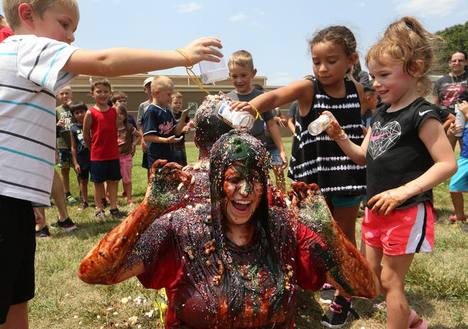 Missionary Katie Rumback reacts to Ignatius Pennycuff, left, Kamille Ortiz, center and Mila Tajchman, right, pouring sprinkles over her during the Human Sundae event of the Totus Tuus Catholic youth program at Our Lady of Guadalupe Catholic Church in South Hutchinson Friday. To see more photos, please visit hutchnews.com.