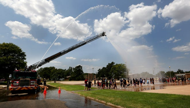 South Hutchinson Fire Dept.'s ladder truck sprays water on the youth participating in the Totus Tuus Catholic youth program Friday afternoon at the Our Lady of Guadalupe Church in South Hutchinson.