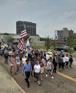 More than 100 people participated in a unity walk Aug. 1 in downtown Alliance, after racially intolerant messages were painted on several buildings.