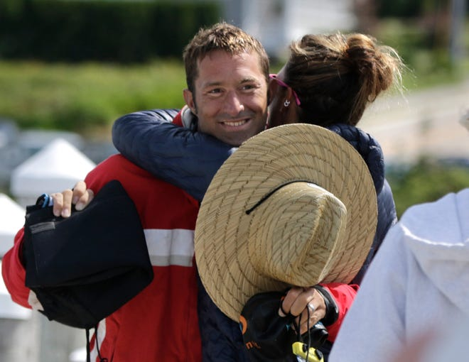 Ben Tuff is greeted by his wife, Gretchen, minutes after touching a buoy off Beavertail State Park in Jamestown to complete his 19-mile swim from Block Island on Sunday.