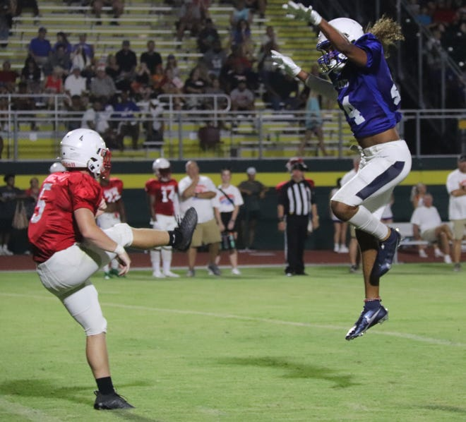 Shawnee's Joe Maytubby (right) leaps through the air on a blocked punt attempt for the East against the West Friday night in the OCA All-State Football Game at OBU's Crain Stadium. Maytubby didn't block the punt but altered it.