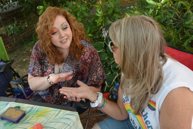 Courtney Wilt (left) reads the palm of Tammy Emerick-Pebley during the Somerset Pride Picnic on Sunday at Trinity Park (Alexis Park) along West Main Street. The event was put together by Pride of Somerset County. It included free a UPMC COVID-19 vaccination clinic, silent auction, entertainment, vendors, music and food trucks.