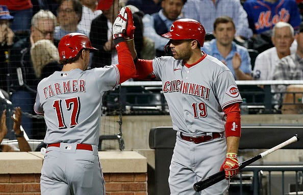 Kyle Farmer #17 of the Cincinnati Reds celebrates his fifth-inning home run against the New York Mets with teammate Joey Votto #19 at Citi Field on July 31, 2021 in New York City.