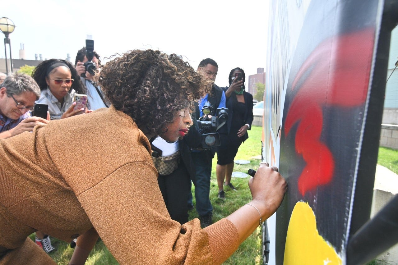 """Actor Jennifer Hudson signs a mural by artist Desiree Kelly outside the Charles H. Wright Museum in  Detroit on Sunday, August 1, 2021 during a conversation for the film """"Respect,"""" in which Hudson plays Aretha Franklin."""