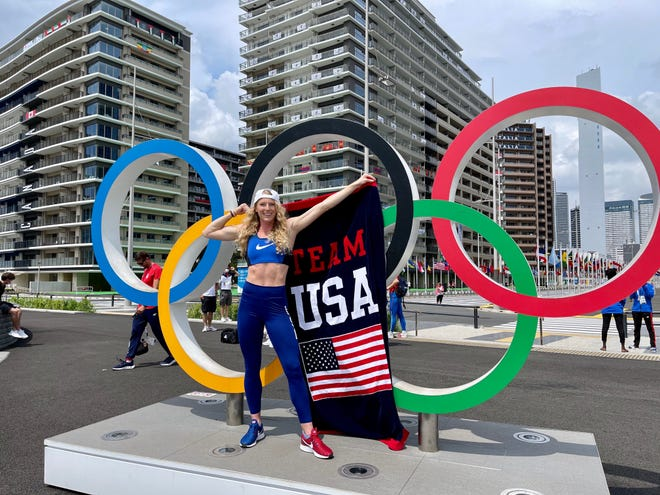 Unmasked for a moment, Greenville Olympian Sandi Morris poses for a quick photo in front of the Olympic rings at Tokyo's Olympic Village.
