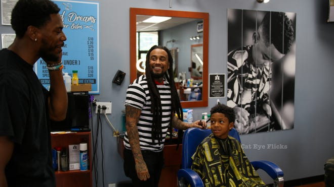 Glenn Robinson III interacts with the community at Faded Dreams Barber and Beauty Salon for a back to school event hosted by the Ari Foundation