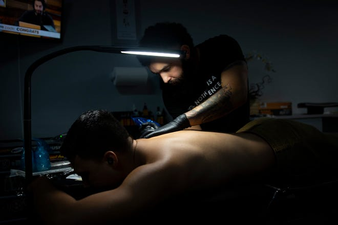Steven Gabriele works on a tattoo for client Jesus Ramirez, Friday, July 30, 2021, at Catharsis Tattoos in Naples.