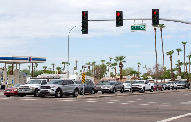 Cars wait to drive during a red light on the intersection of 51st Avenue and Camelback Road in Glendale on July 31, 2021