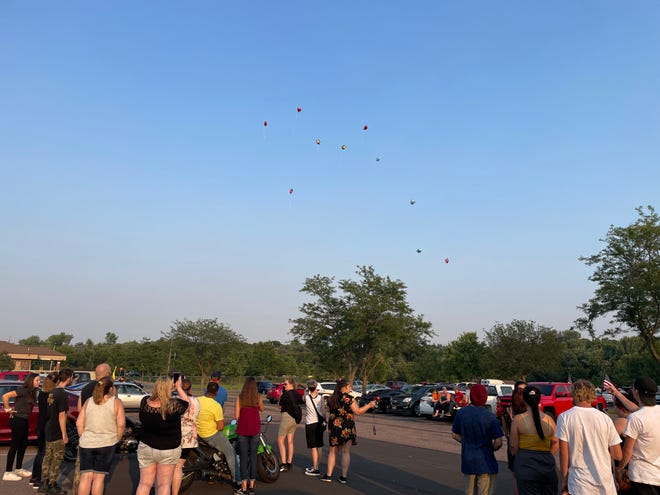 Mourners watch balloons float away to honor the three young people killed in a rollover crash on I-229 at a memorial service on Saturday July 31, 2021.