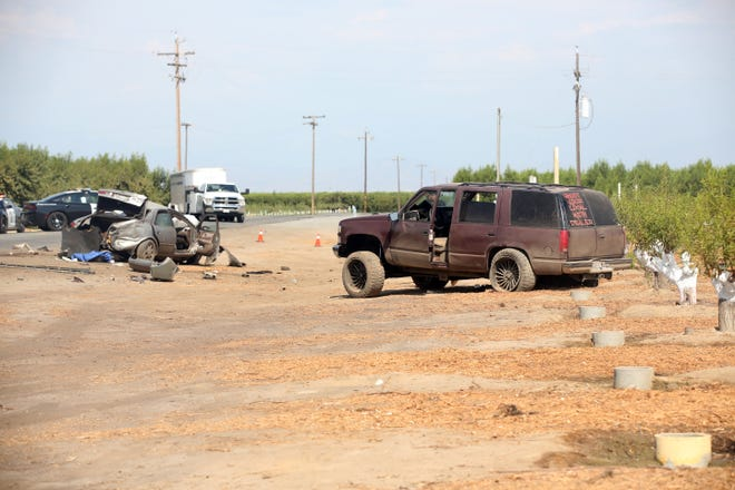 A Camry and Chevy Tahoe await tow trucks ordered by CHP officers during an investigation of a 3-car crash that left three people dead near Road 52 and Ave. 368 in Tulare County on July 31, 2021.