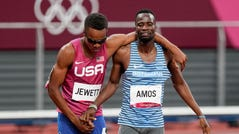 Isaiah Jewett, of the United States, and Nijel Amos, right, of Botswana, shake hands after falling in the men's 800-meter semifinal at the 2020 Summer Olympics, Aug. 1, 2021, in Tokyo.