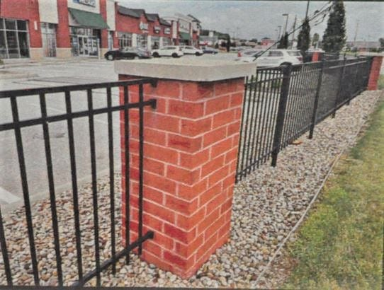 This is an example of the fence and brick pillars which could be erected along Route 8 and North Plaza Drive around the former PNC Bank property.