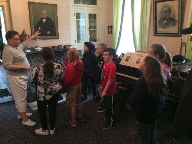 Elaine Dunlap, a member of the Alliance Historical Society board, points out historical items in the Mabel Hartzell Home to a class of youngsters prior to the COVID-19 pandemic.